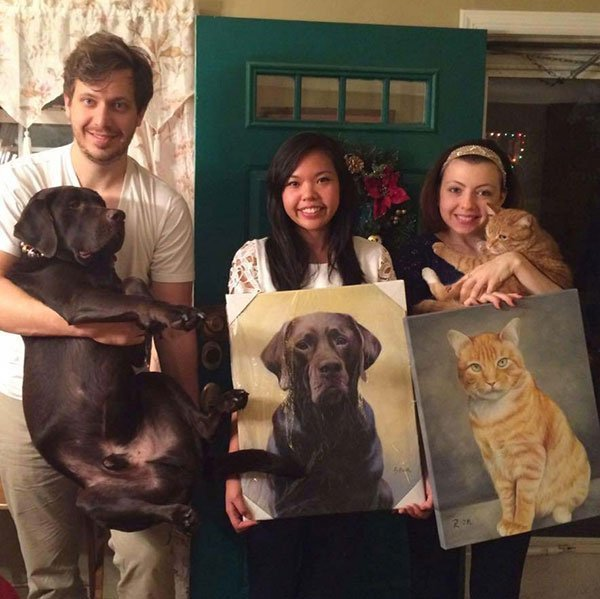 A family poses with both their pets and their beautiful custom oil paintings of the same animals they're posing with.
